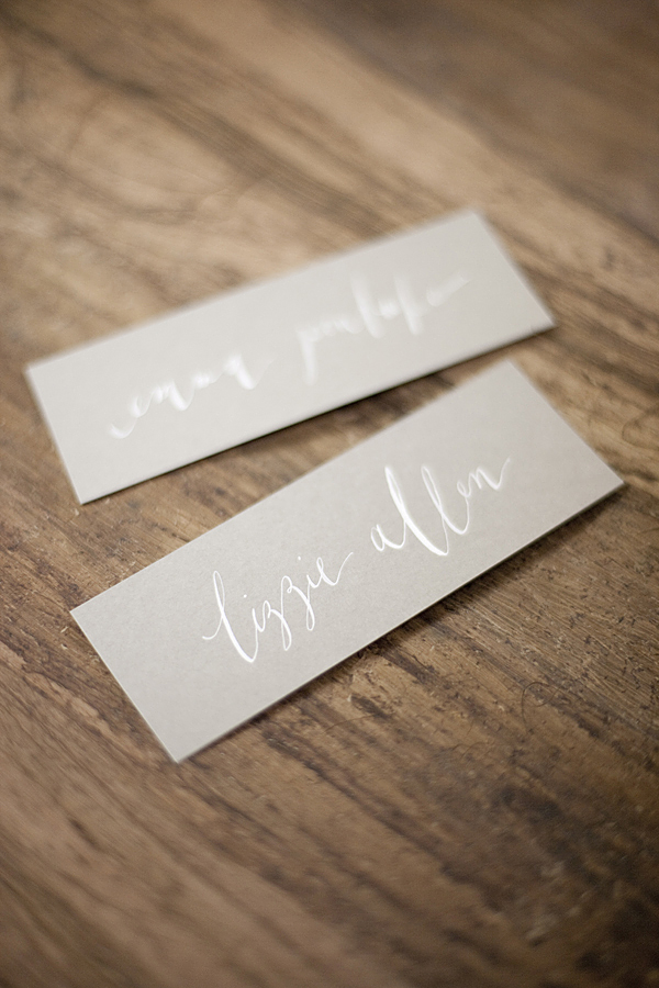White ink calligraphy on grey paper place cards