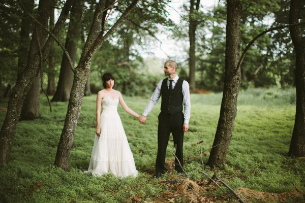 Wedding couple standing in mossy field under trees